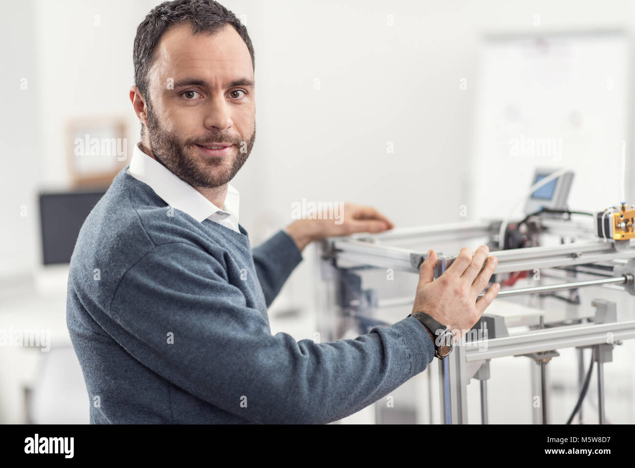 Pleasant young engineer posing with 3D printer in office - Stock Image