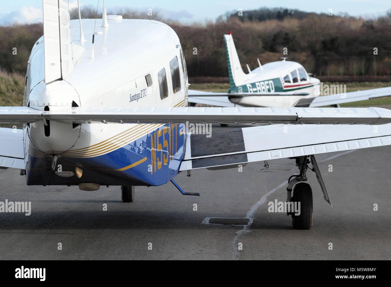 General aviation busy at airfield Piper Pa-32 Saratoga and behind Piper Pa-28 Cherokee aircraft taxying at a UK - Stock Image