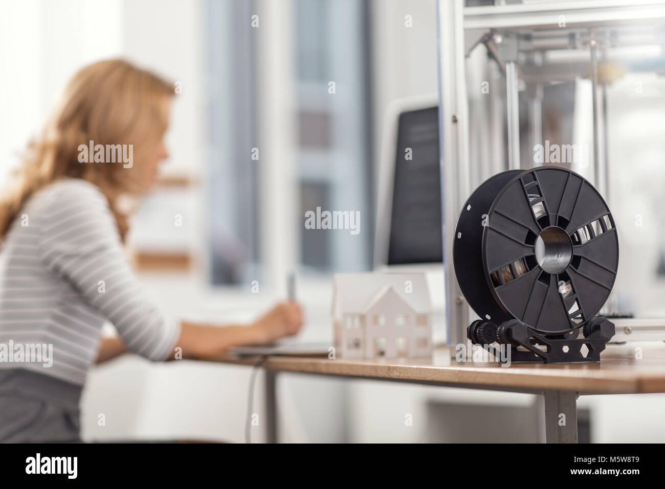 Spool with filament standing on the work desk - Stock Image