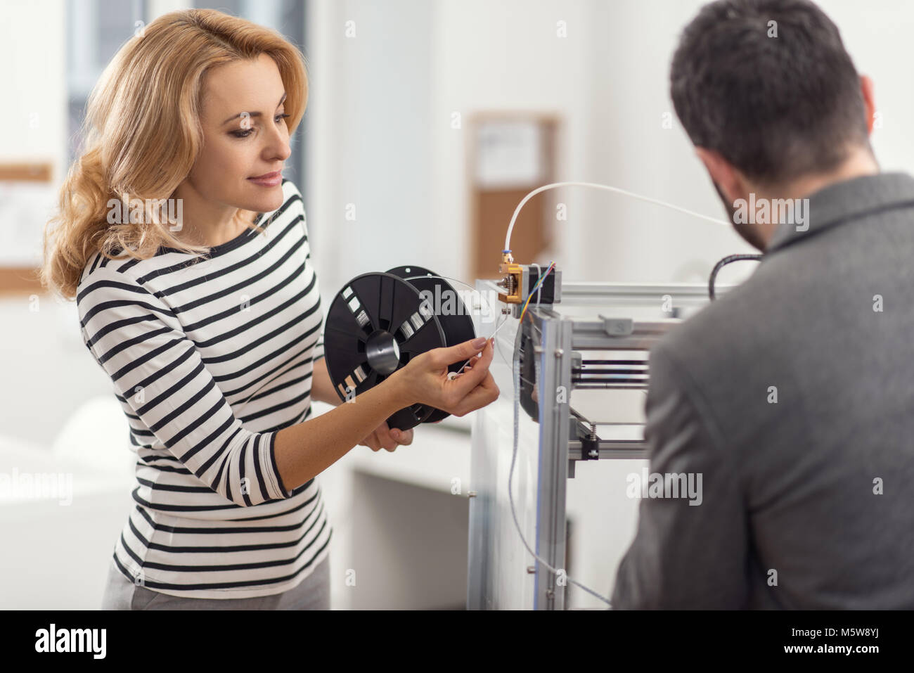Beautiful woman holding spool and inserting filament - Stock Image