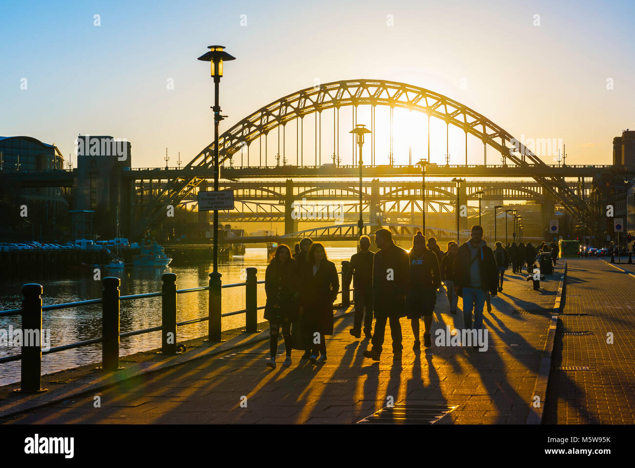 Newcastle Tyne Bridge, view at sunset of people walking in the quayside area of Newcastle, England, with the iconic - Stock Image