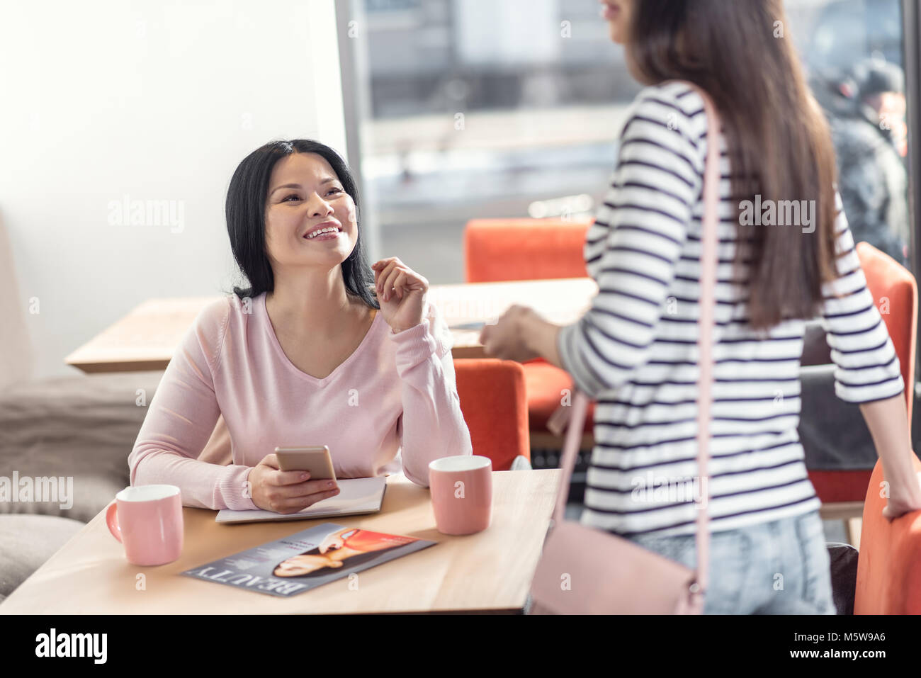 Attractive delighted woman turning to you - Stock Image