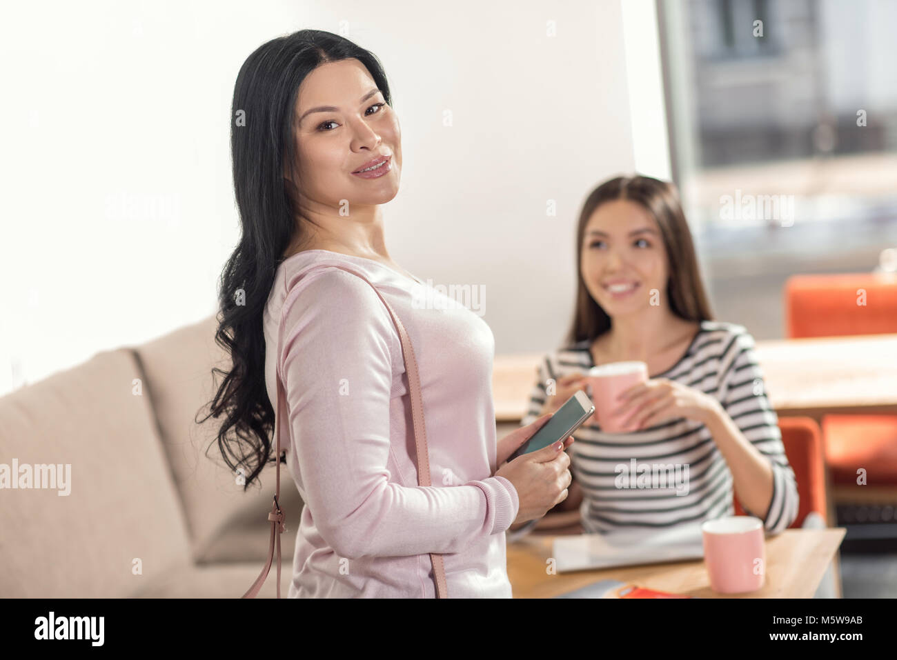 Positive nice woman standing behind her friend - Stock Image