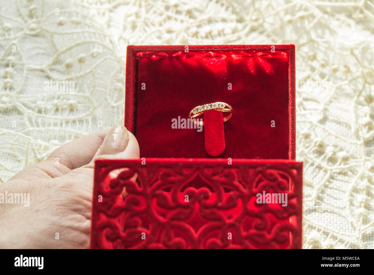 Female hand holding a red box with a ring on the background of the lace napkin, selective focus - Stock Image