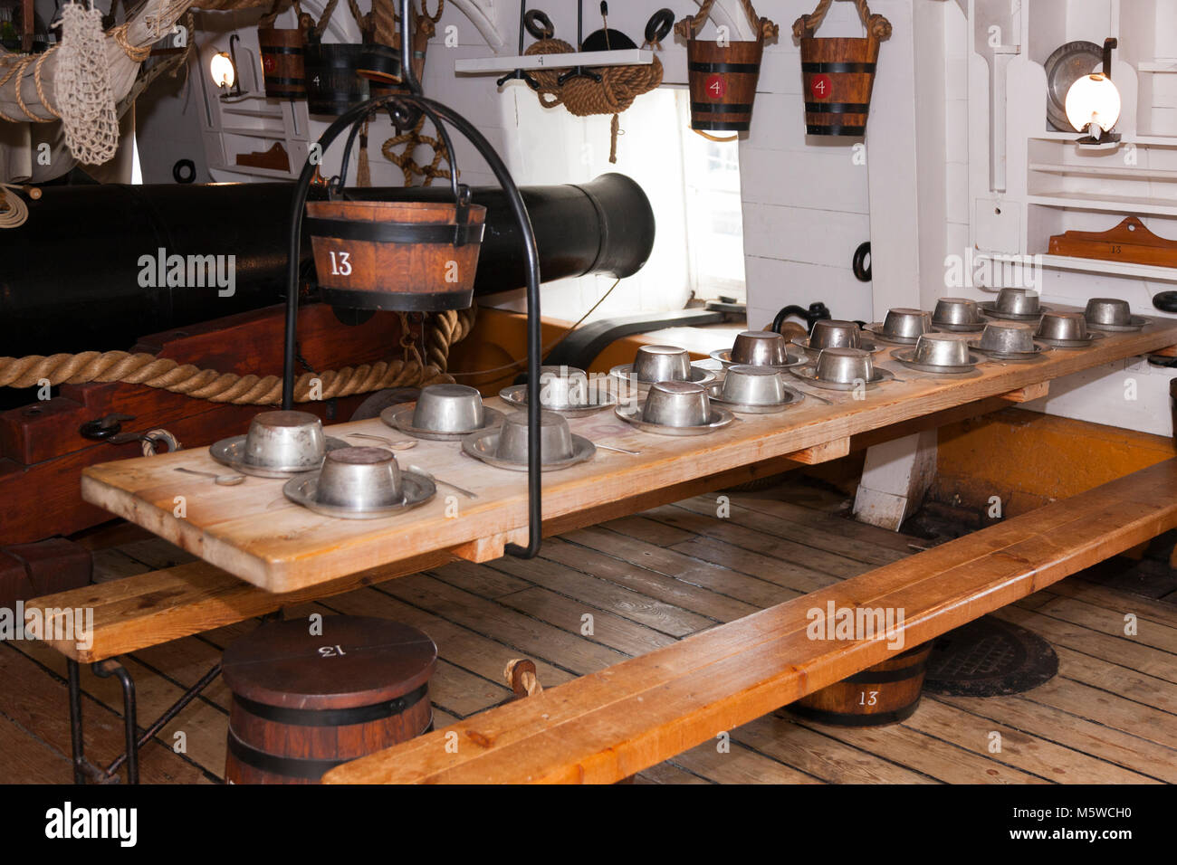 A sailors laid mess table ( historical recreation ) between cannon / guns on the Gun Deck of HMS Warrior. Portsmouth - Stock Image