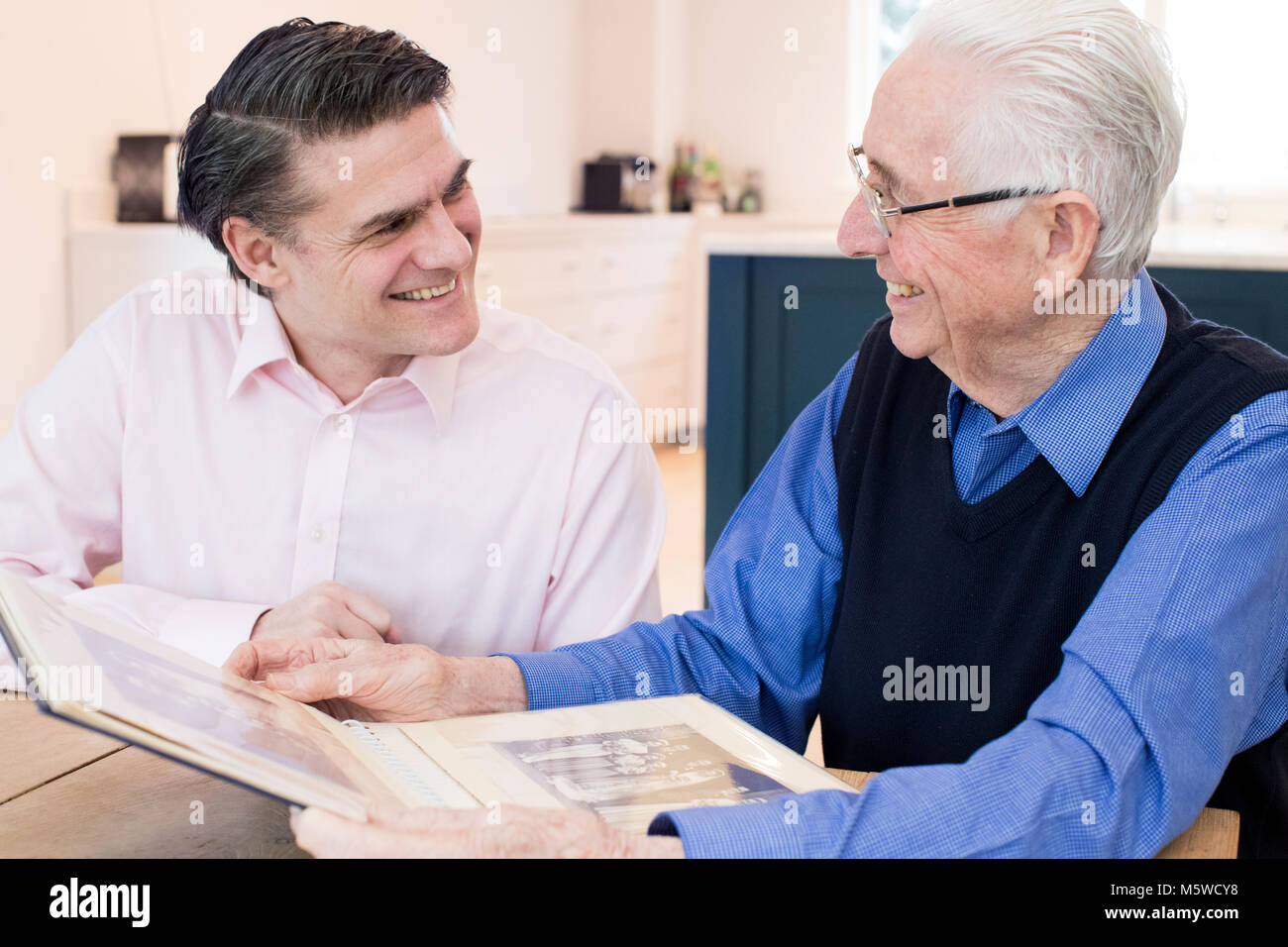 Senior Man Looking At Photo Album With Adult Son - Stock Image