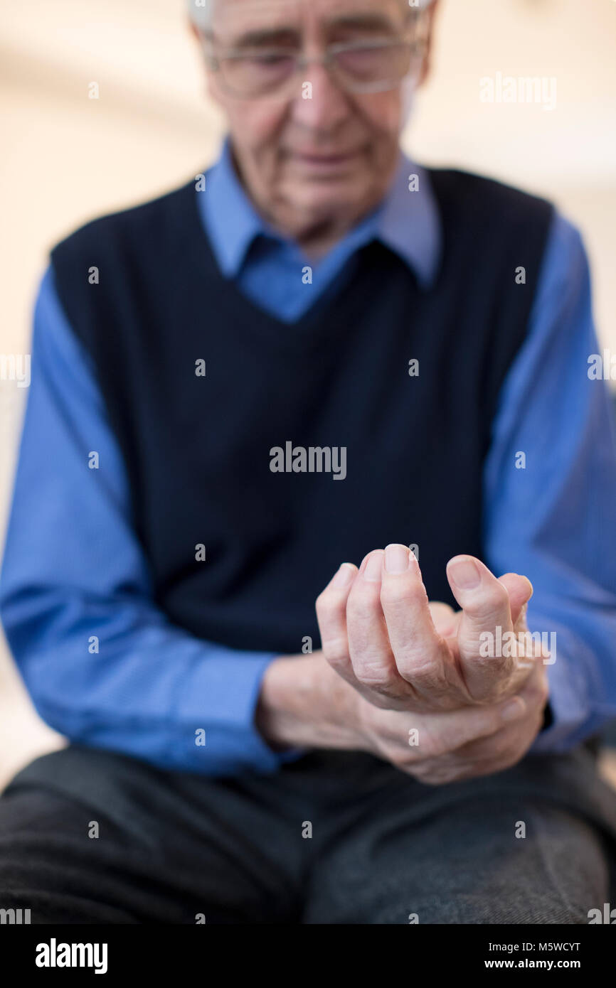 Senior Man At Home Suffering With Arthritis - Stock Image