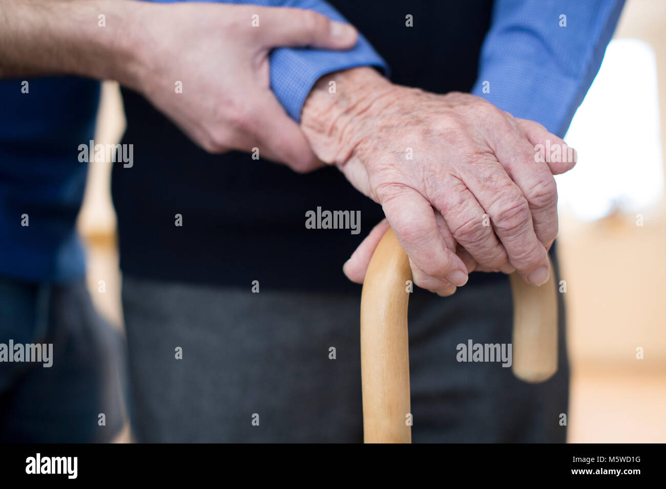 Senior Man's Hands On Walking Stick With Care Worker In Background - Stock Image