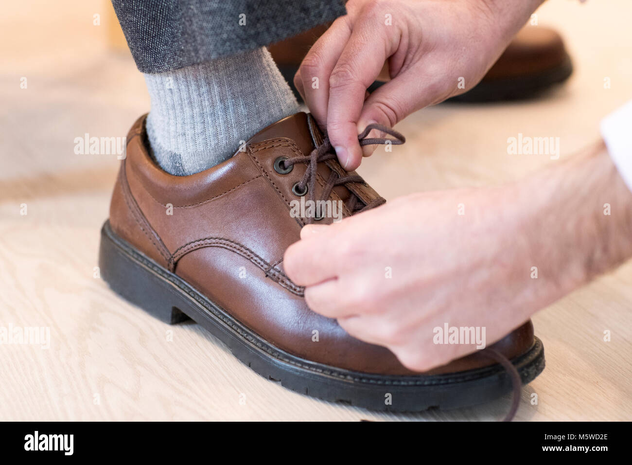 Close Up Of Adult Son Helping Senior Man Tie Shoelaces - Stock Image