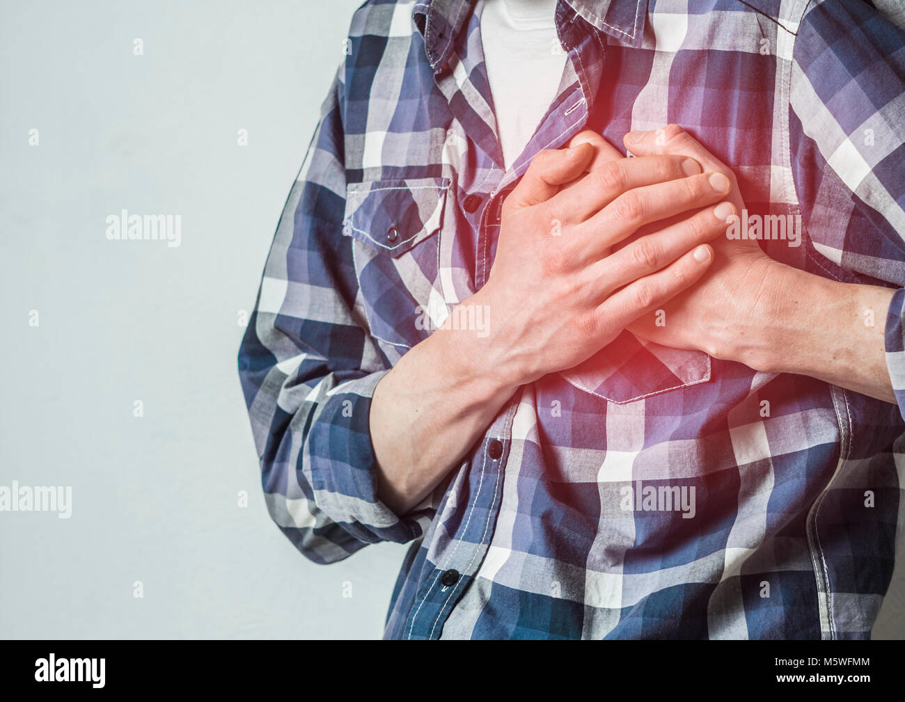 Heartache. A man holds on to his chest. A heart attack. Stroke. - Stock Image