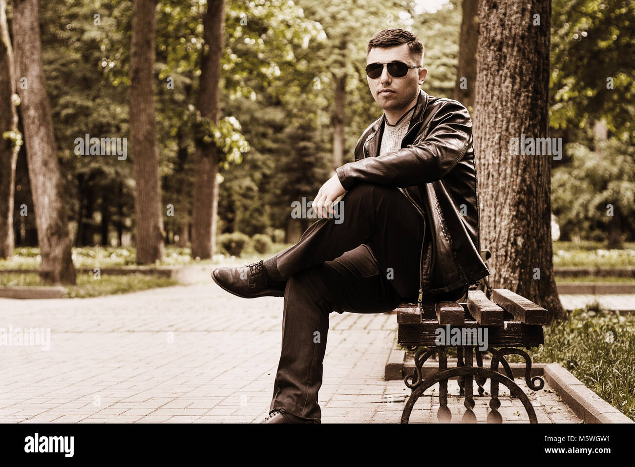 Tinting a photo in brown tones with a young man in a park in sunglasses and a leather jacket - Stock Image