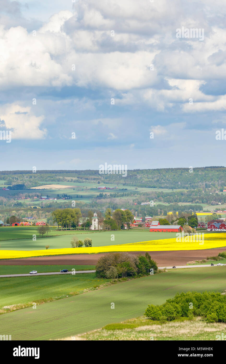 Rural view of the field with a road and a village church - Stock Image