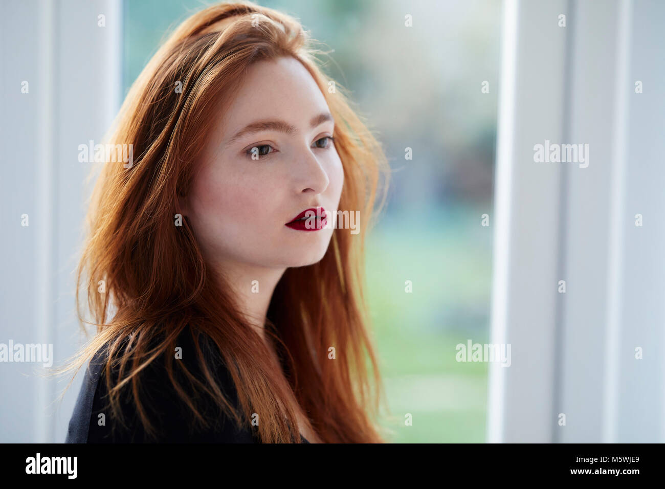 Attractive red haired girl thinking - Stock Image