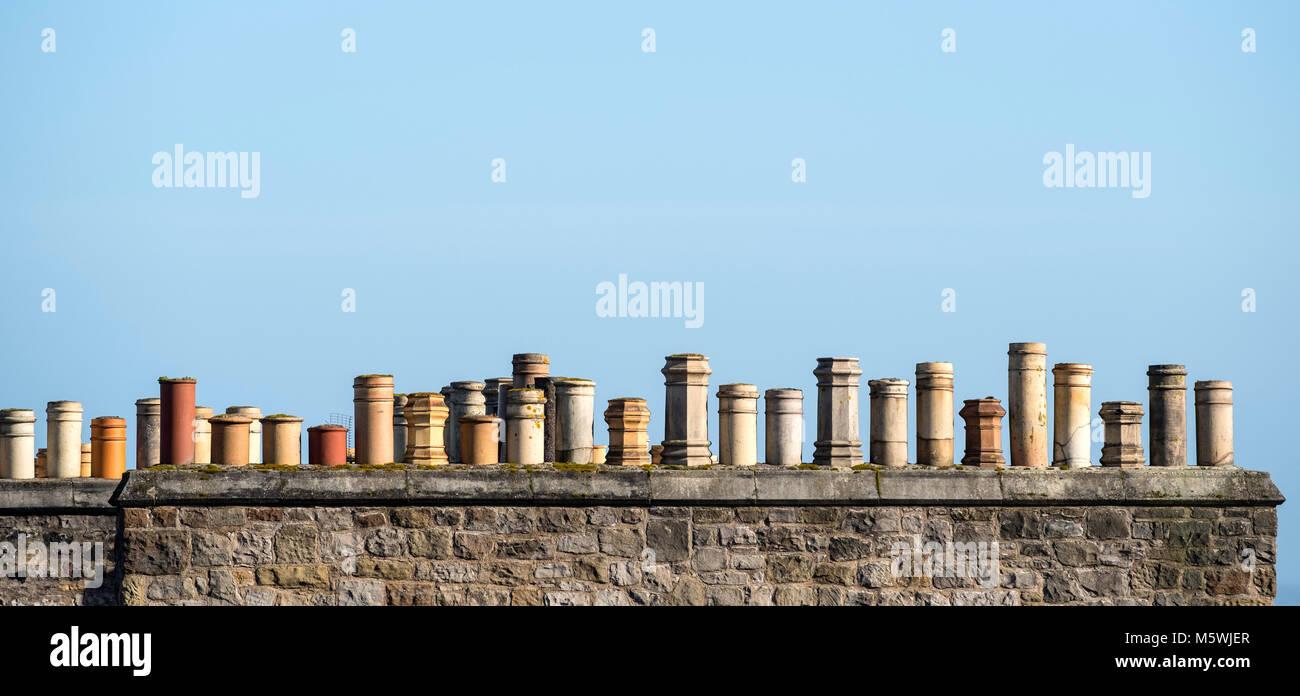 Row of old chimney pots on a house in Edinburgh, Scotland, United Kingdom - Stock Image