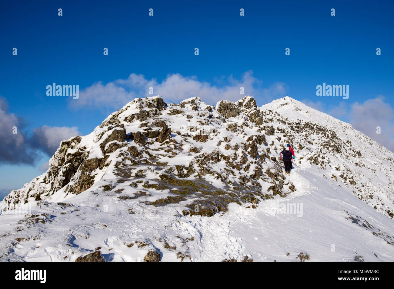Hikers hiking down south ridge at Bwlch Main from summit of Mt Snowdon peak with snow in winter in Snowdonia National Stock Photo