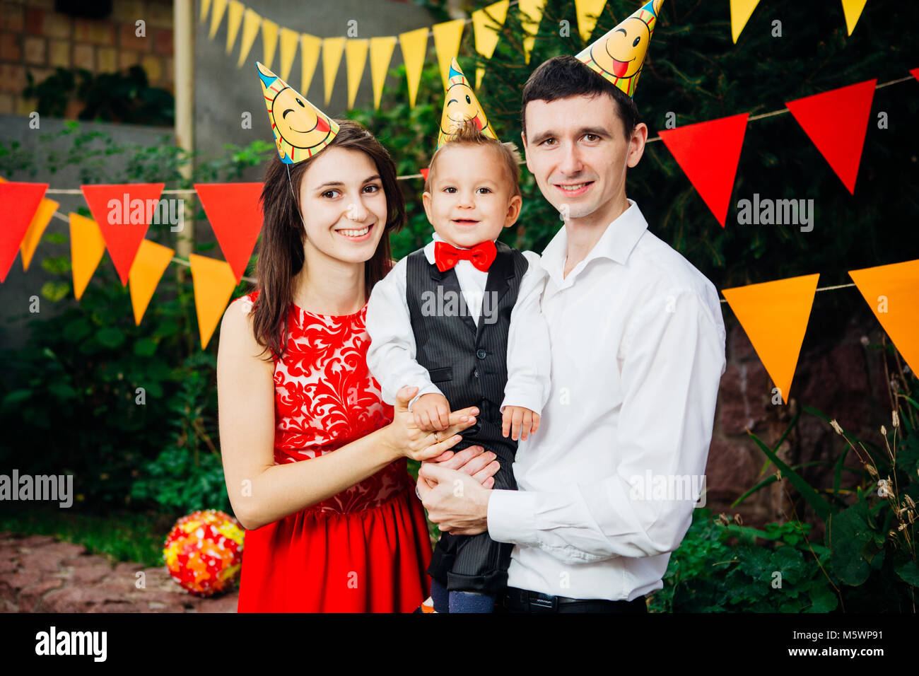 theme children birthday party. Family father and mother holding son of one year on the background of greenery and - Stock Image