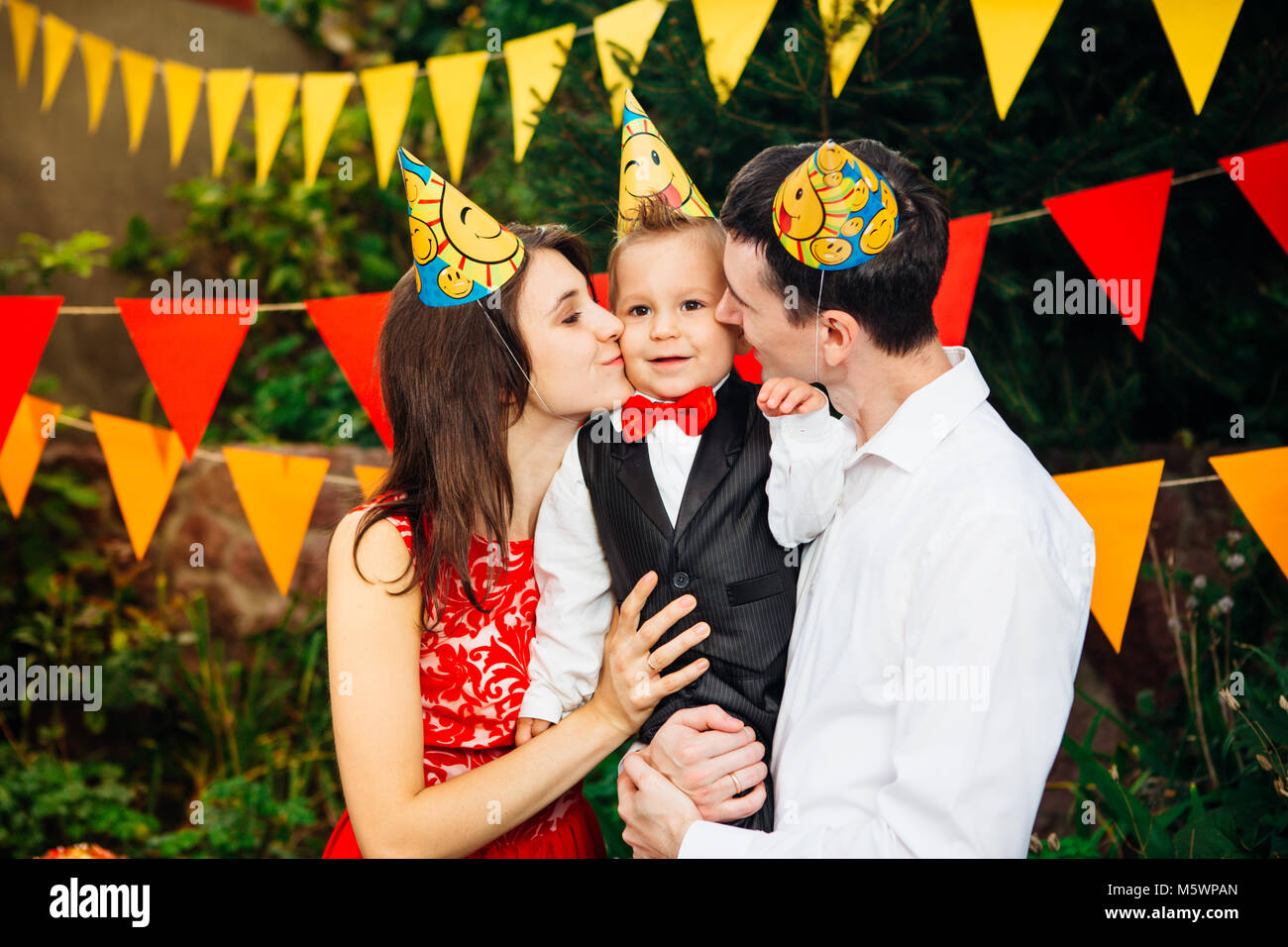 children birthday party. Family father and mother hold son of one year of birth in arms and kiss cheekin the background - Stock Image