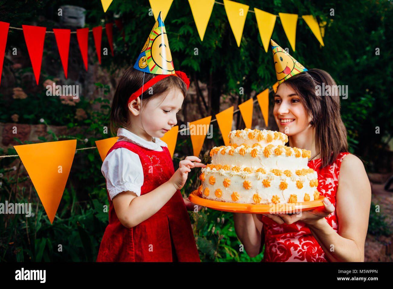 Children's party and cake. A small child of a funny girl is trying to finger a large two-story cake that mom near Stock Photo