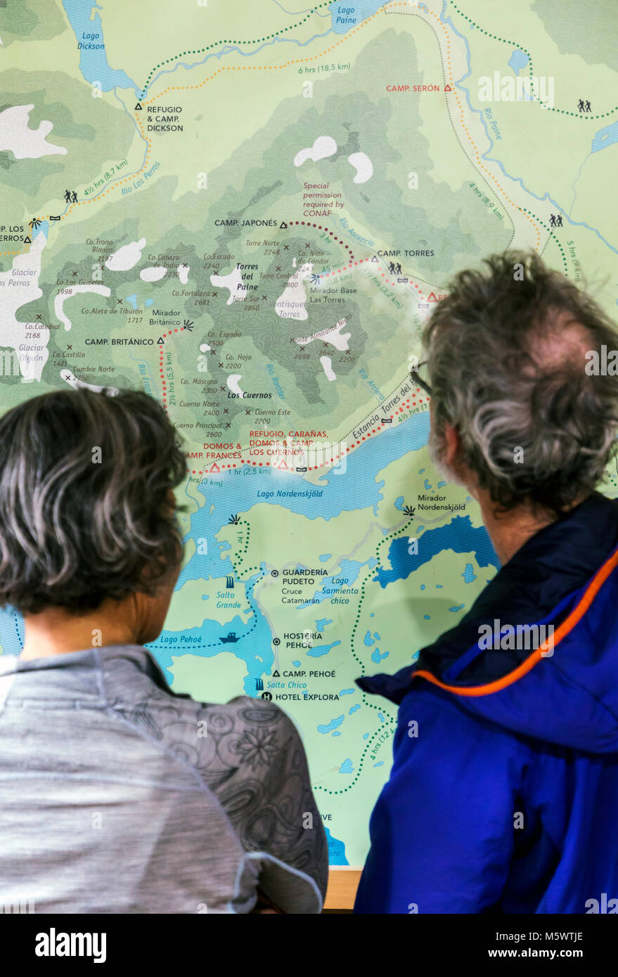 Trekkers examine wall map; Refugio El Chileno; Torres del Paine National Park; Chile - Stock Image