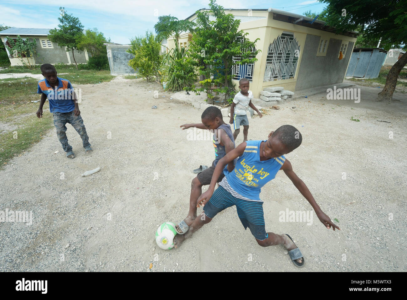 Children play in front of a house built by Servicio Social de las Iglesis Dominicanas in the Haitian community of - Stock Image