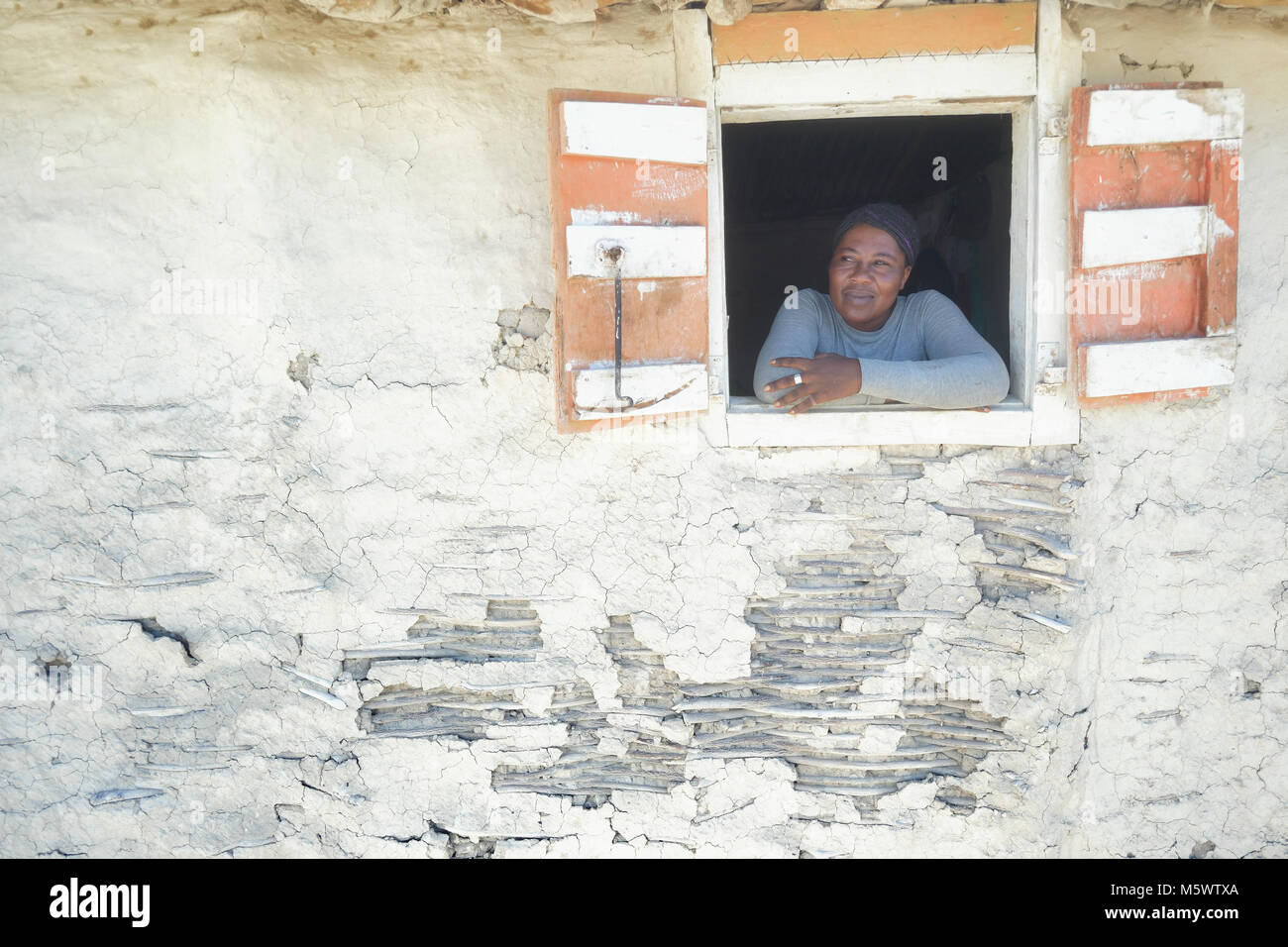 Michel Louis Marie looks out the window of a house in the Haitian community of Ganthier. - Stock Image
