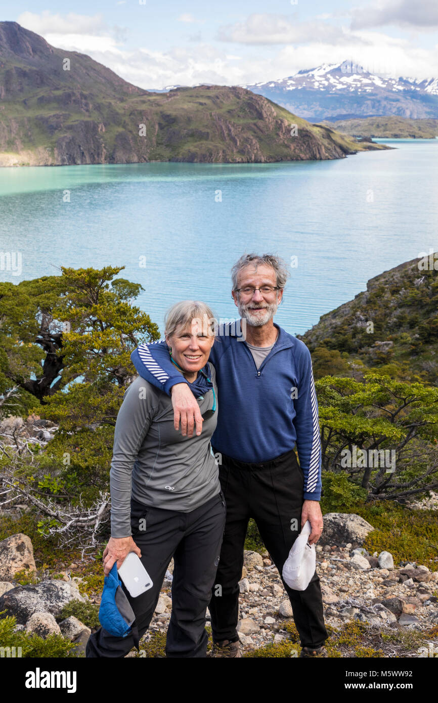 Married couple pose for photograph; Lago Nordenskjold beyond; Torres del Paine National Park; Chile - Stock Image