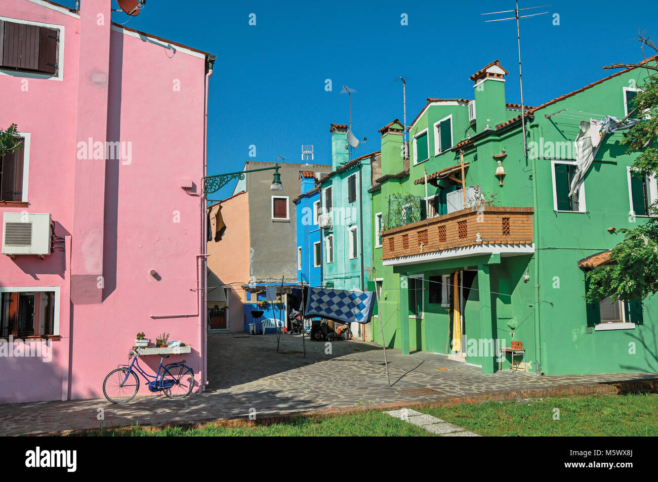 View of colorful terraced houses, balcony and clothes hanging in an alley on sunny day in Burano, a gracious little Stock Photo