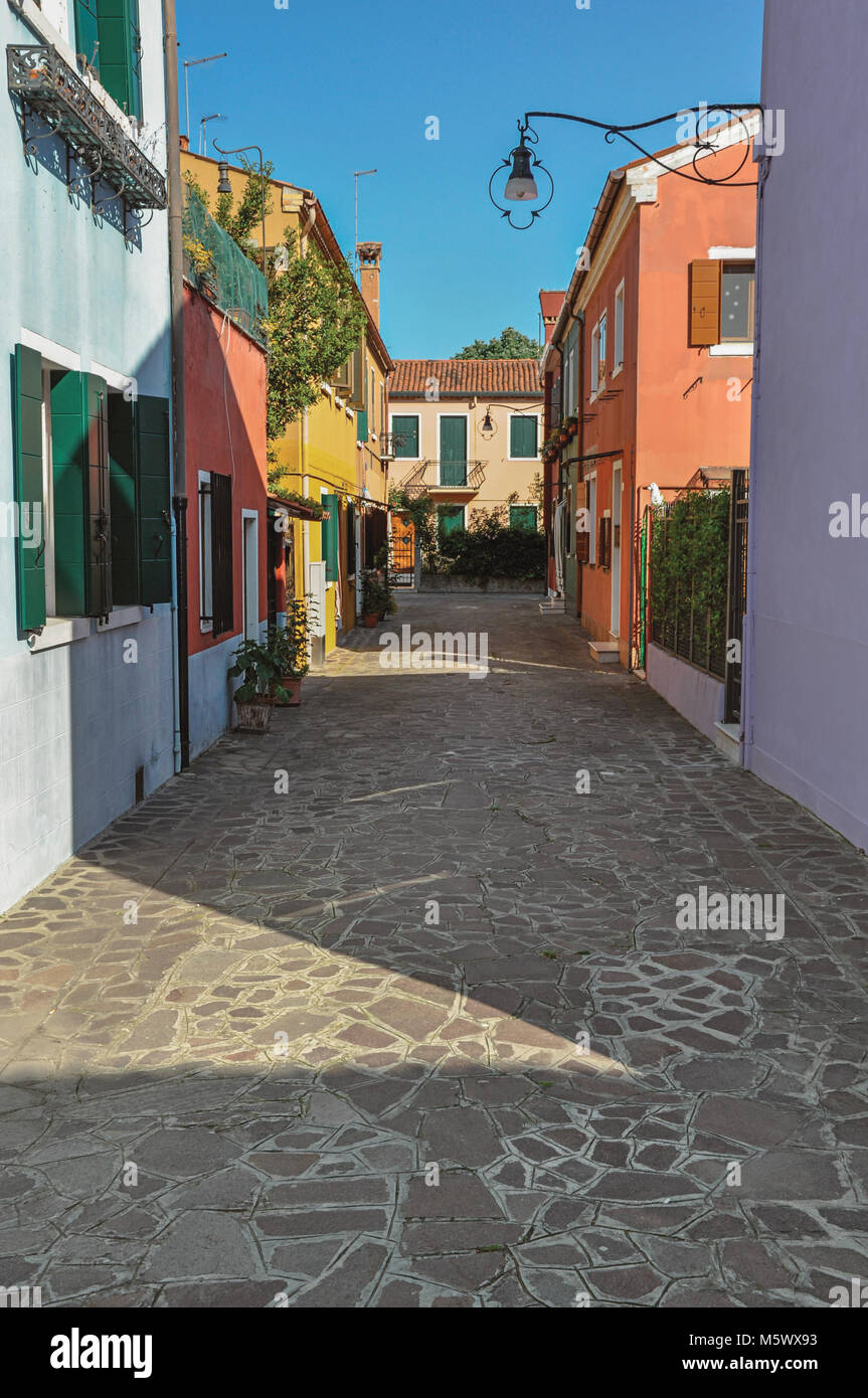 Overview of colorful terraced houses, lamp and bushes in an alley on sunny day in Burano, a gracious little town Stock Photo