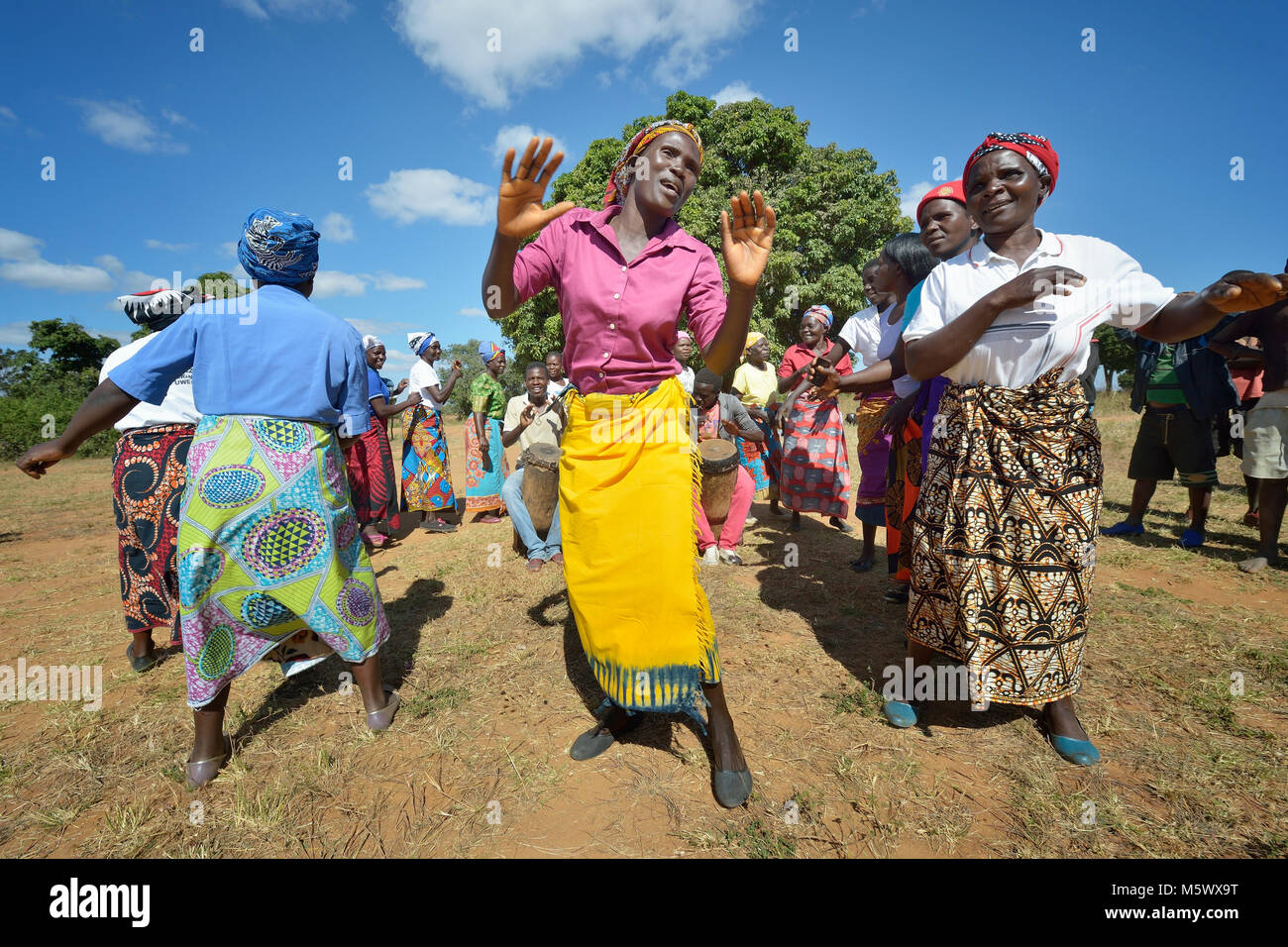 Women sing and dance as part of an education program promoting proper prenatal care and maternal health in Kayeleka - Stock Image