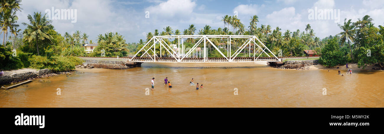 People bathing in river, somewhere between Galle and Colombo, Sri Lanka - Stock Image