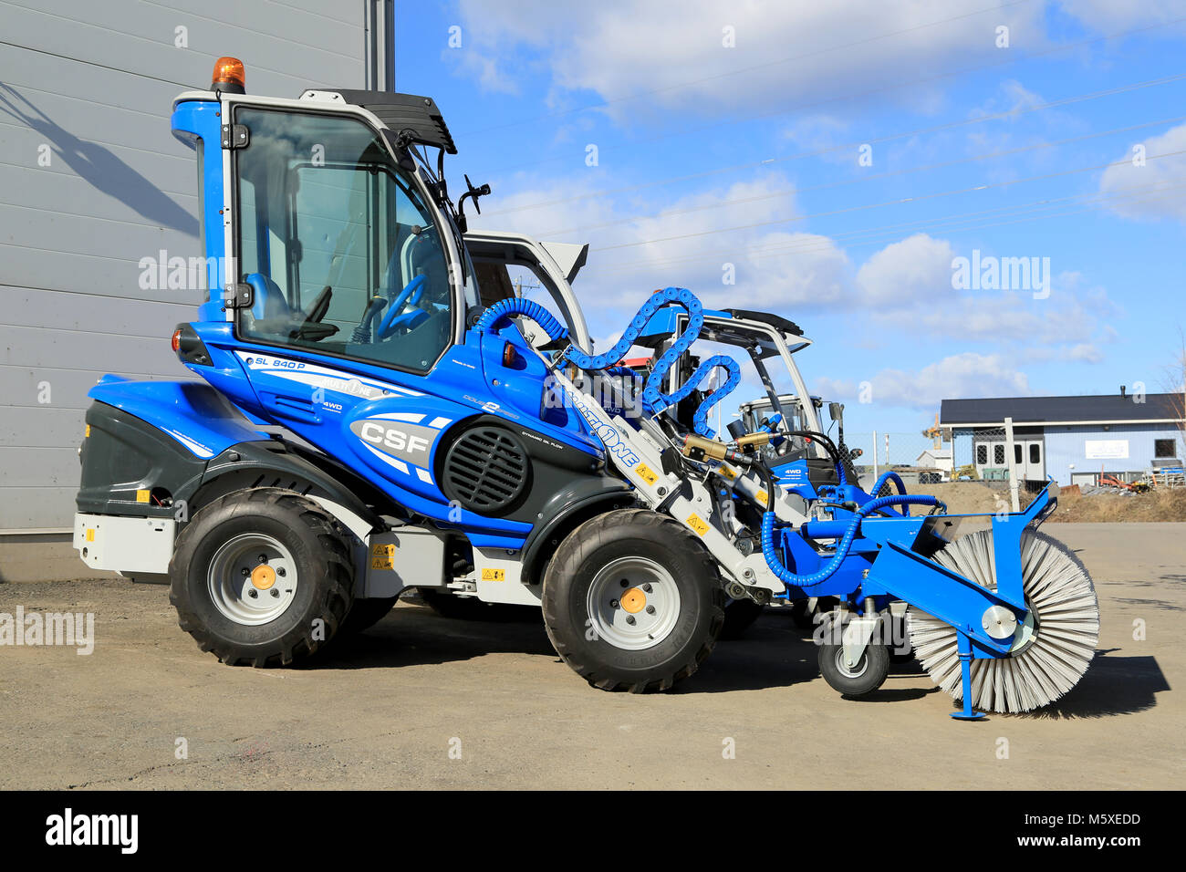 TURKU, FINLAND - MARCH 21, 2015: Multione compact miniloader with a brush attachment outside on a yard. Multione - Stock Image