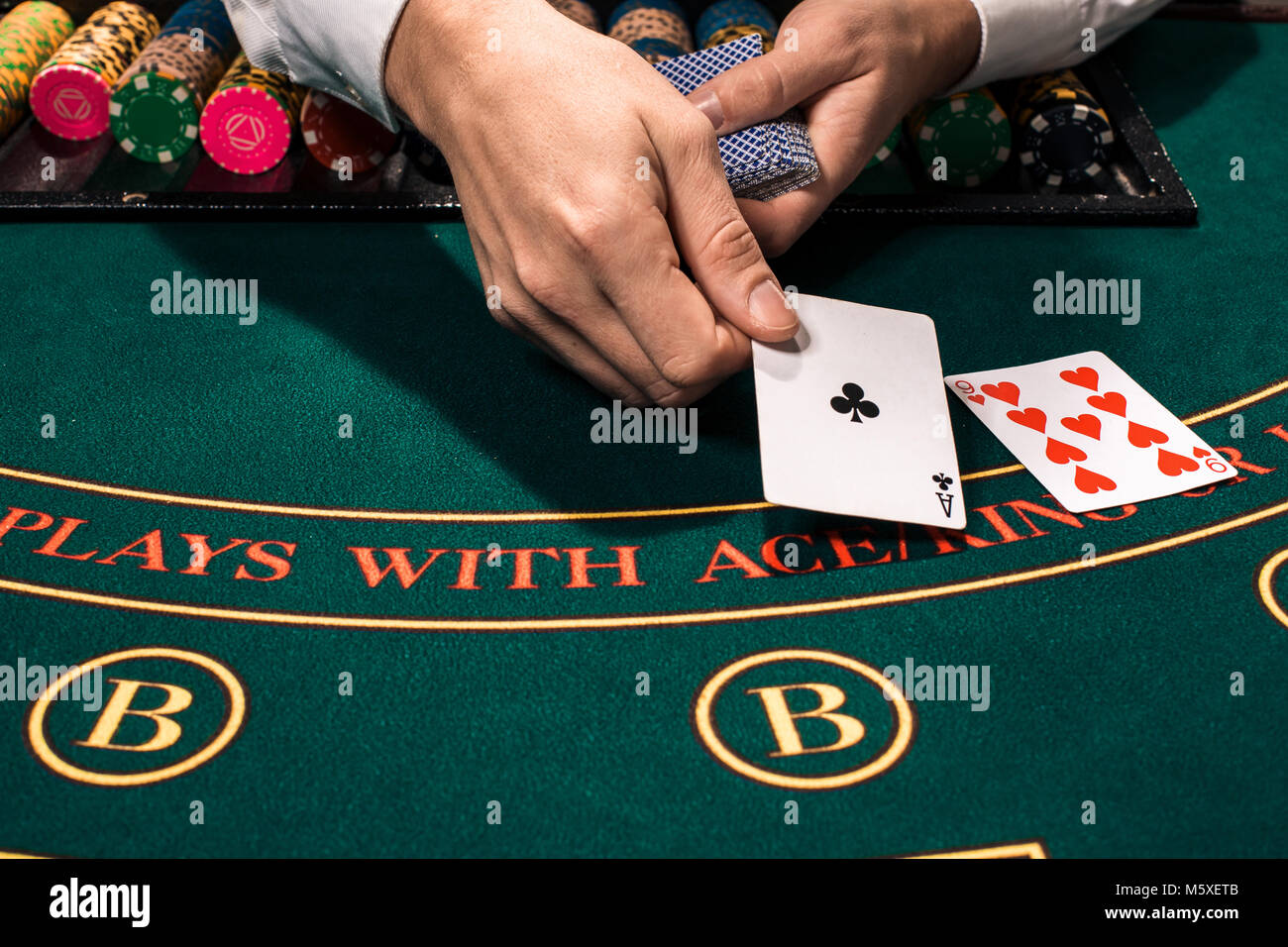 Close up of holdem dealer with playing cards and chips on green table - Stock Image