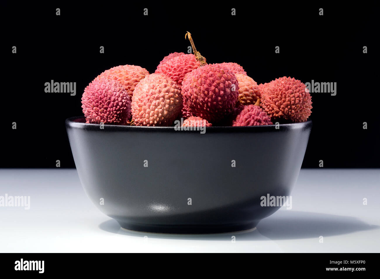 lychee fruits in a bowl isolated on dark background - Stock Image