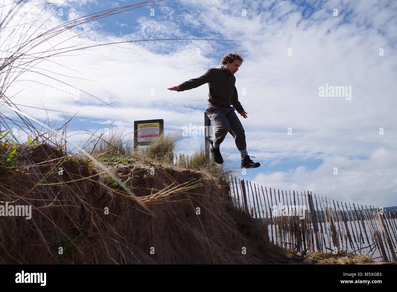 Ruggedly Handsome British Explorer, Dressed in Green Leaping from Sand Dunes on Dawlish Warren Nature Reserve. South - Stock Image