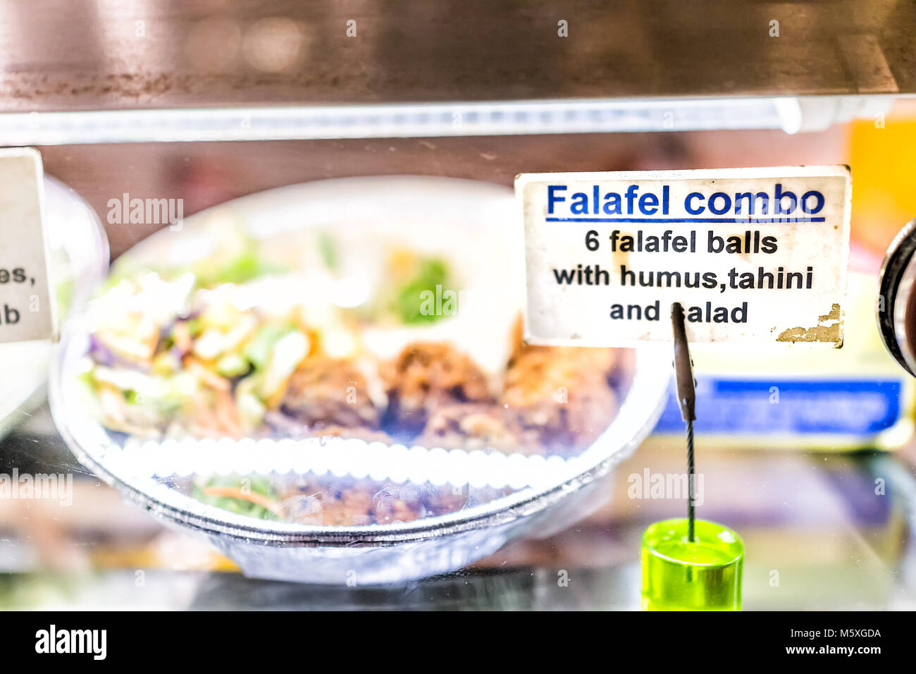 Packaged falafel balls middle eastern take away fast food bowl, hummus, tahini, salad on display behind glass window - Stock Image