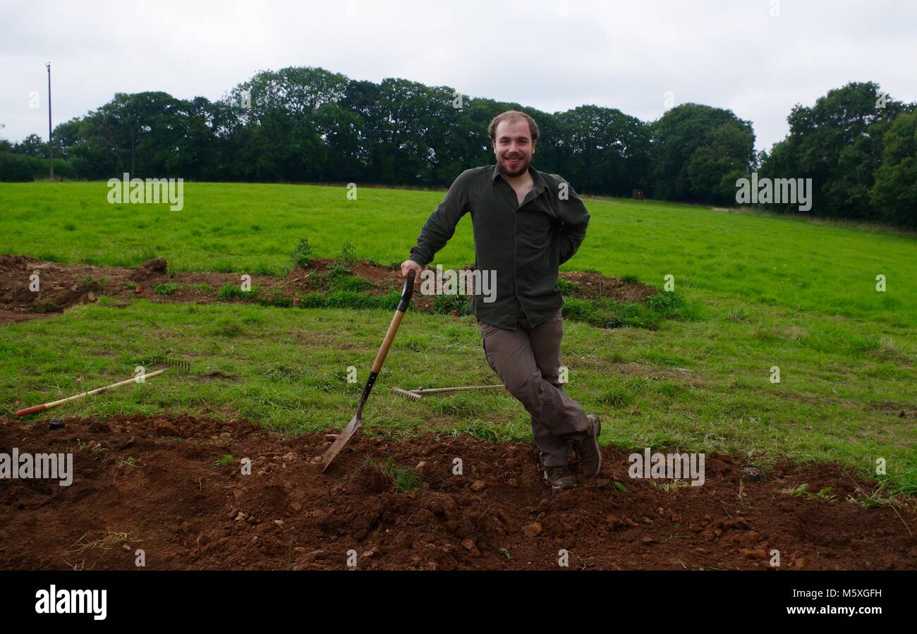 Young Handsome Man Manually Digging a Grassy Field in Mid Devon to Build a Poly Tunnel. Lydcott Nursery, Morchard - Stock Image