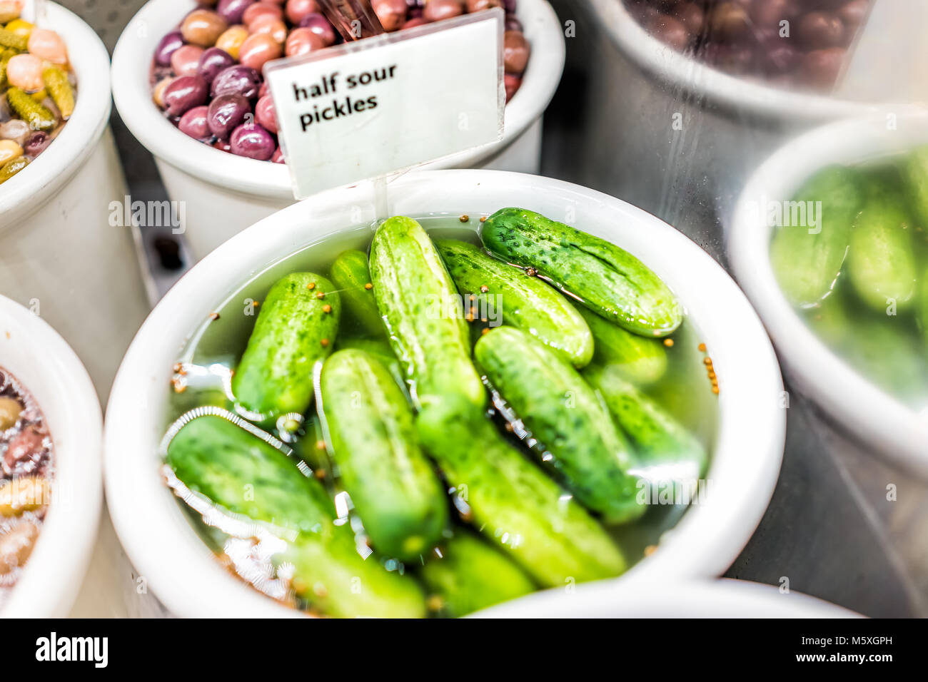 Closeup of plastic container jar filled with bulk green half sour pickles, mustard seeds in vinegar brine, sign - Stock Image