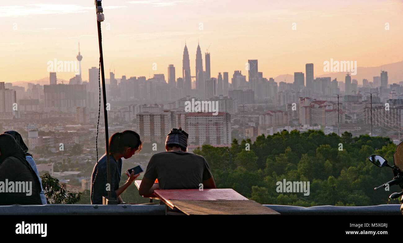 Kuala Lumpur, Malaysia. September 14, 2017. Iconic skyline of Kuala Lumpur at sunset with a young couples distracted - Stock Image