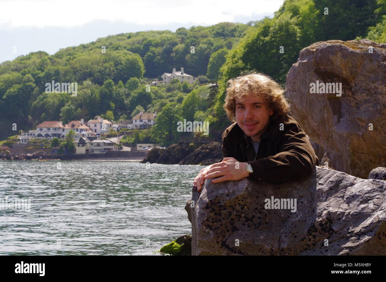 Long Haired Teenage Boy Posing on the Coast with Babbacome Beach in the background, English Riviera, Torquay, South Stock Photo