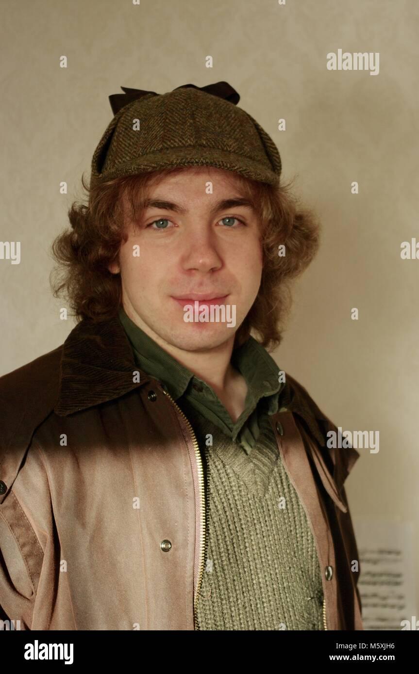 Young Attractive British Man Dressed as Sherlock Holmes in Deerstalker Tweed Hat. Exeter, Devon, UK. - Stock Image
