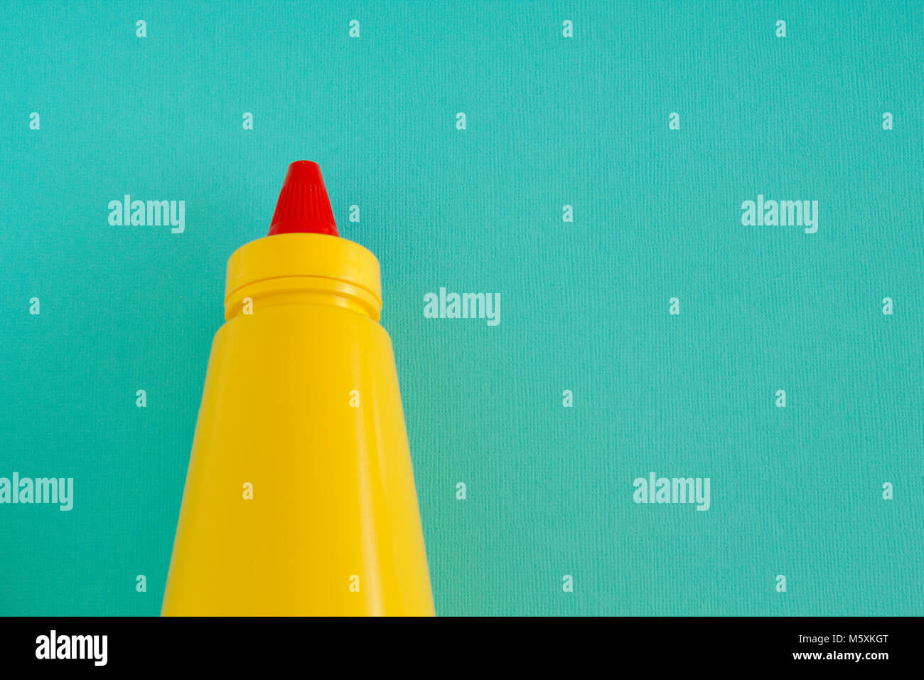 A bright yellow squirting mustard or condiment bottle with bright red twisting lid. Left aligned on an aqua background. - Stock Image