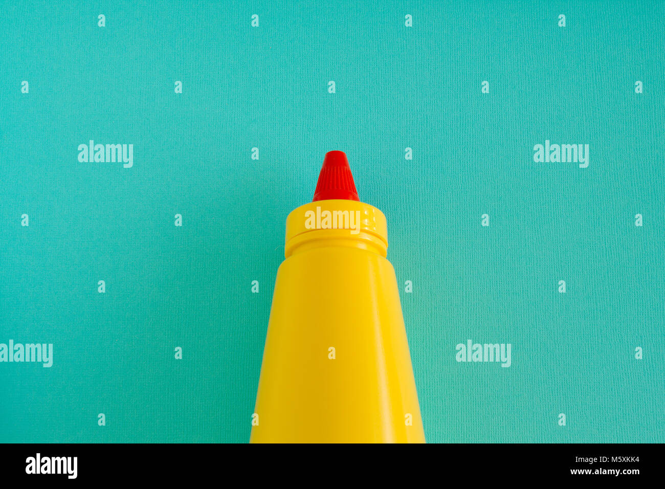 A bright yellow squirting mustard or condiment bottle with bright red twisting lid. Centre aligned on an aqua background. - Stock Image