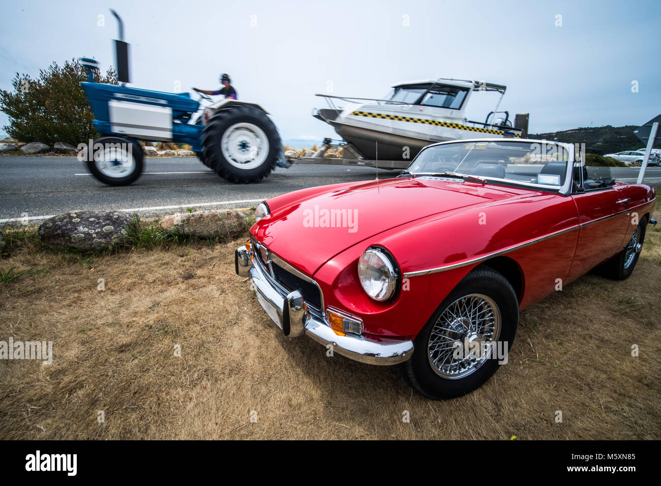 Exotic red Convertible car in front of tractor pulling boat - Stock Image