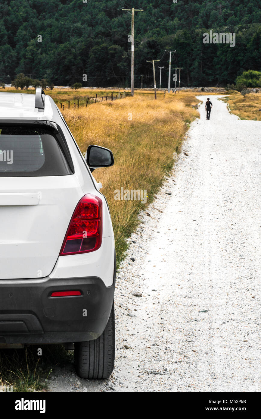 Woman walking away from parked car in rural countryside - Stock Image
