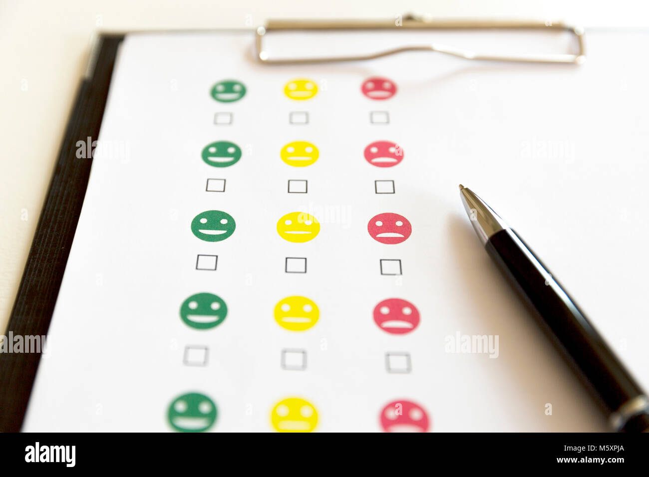 Customer service evaluation survey with smiley faces and pen. - Stock Image