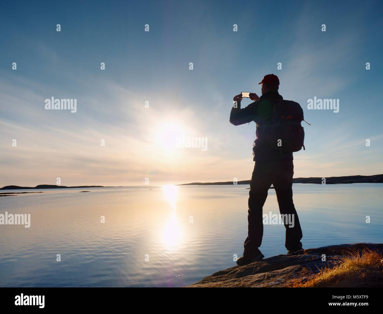 Tourist with phone in hand and backpack stand on a rock. Hiker looking over blue sea and taking photo by his smart - Stock Image