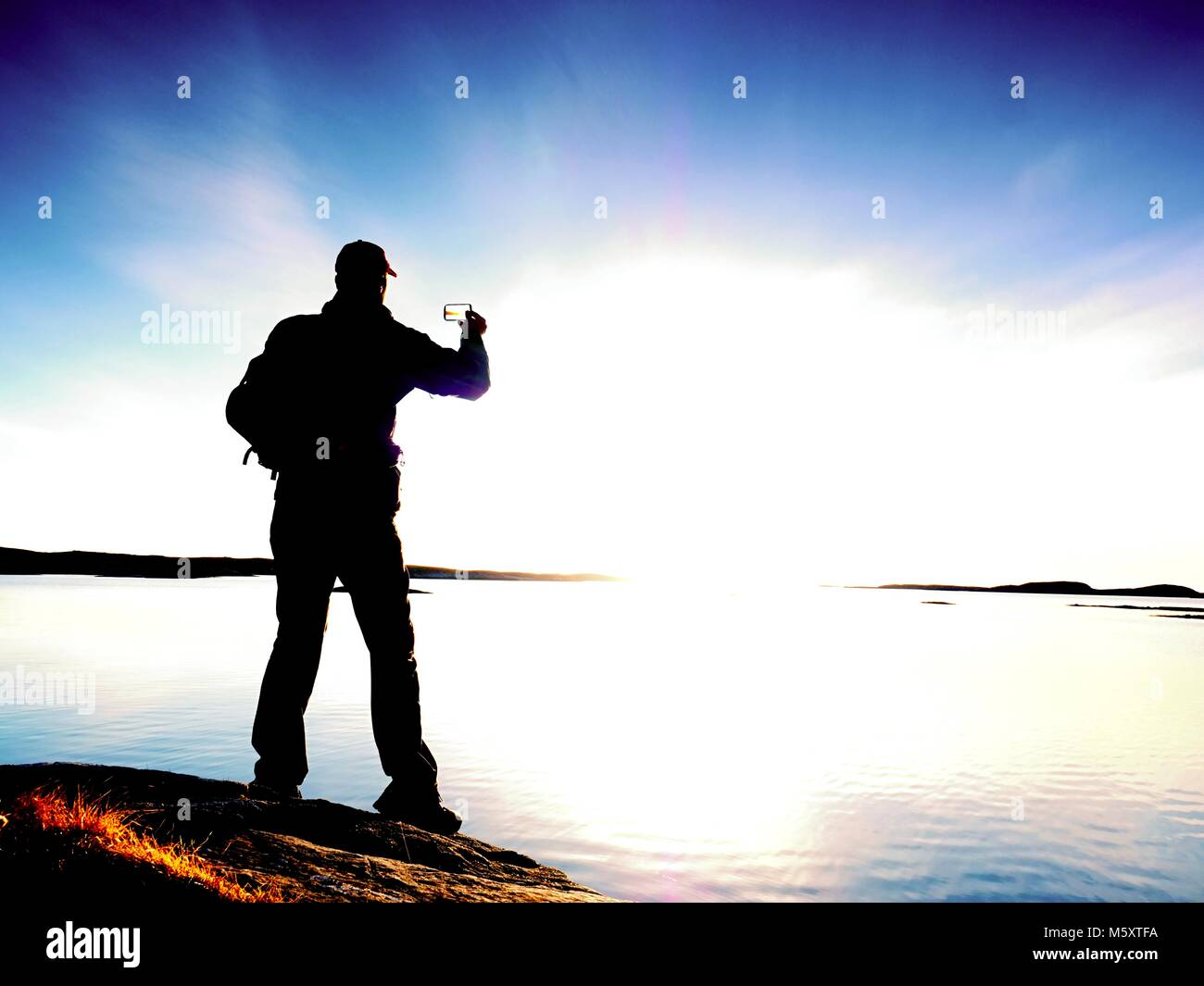 Silhouette of man keep memories with camera phone in his hand. Marvelous sunset at sea, smooth water level - Stock Image