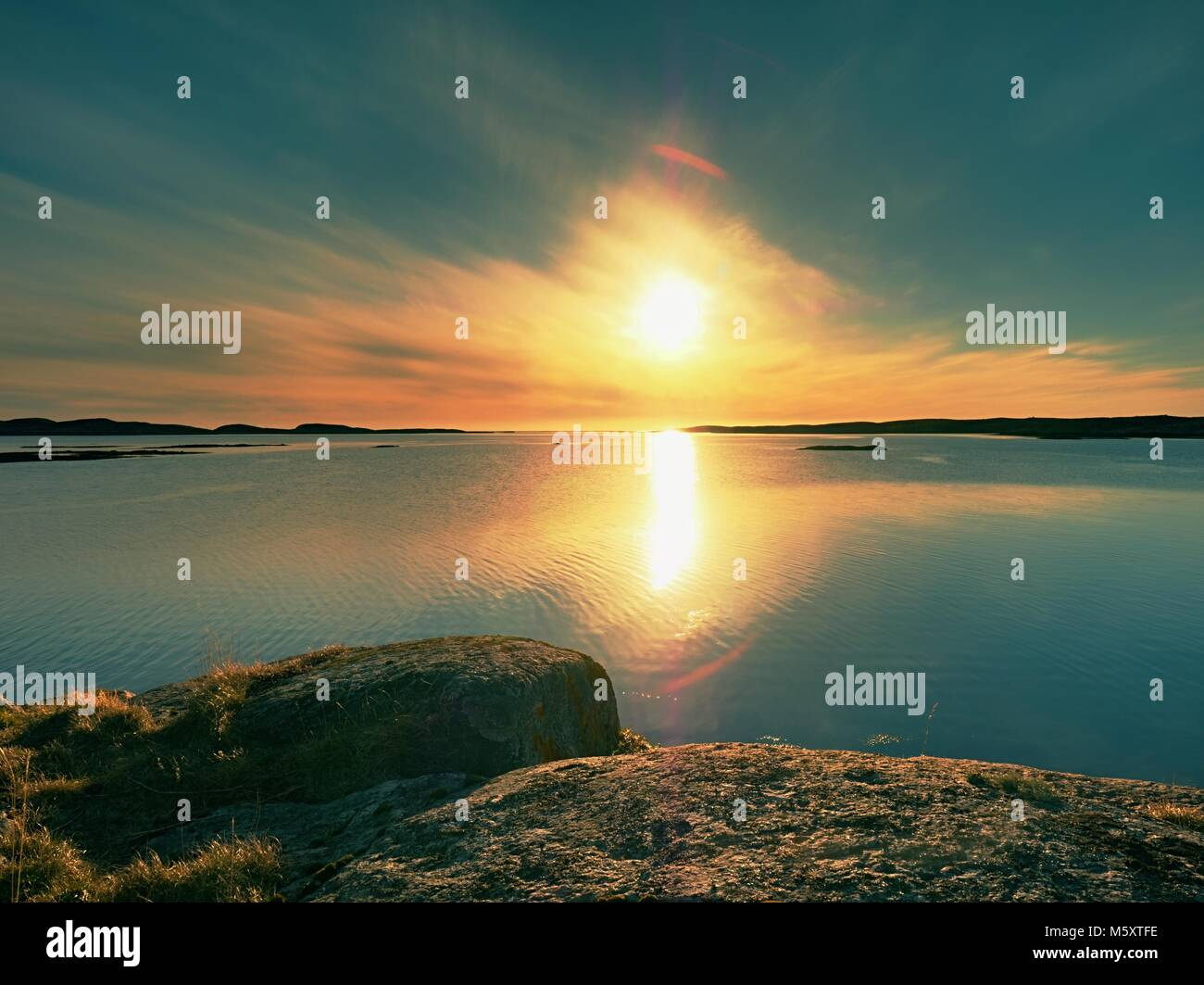 Mysteries of dawn. Sea sunrise above the Sea coast, silent water level. Clear blue sky in holiday resort - Stock Image