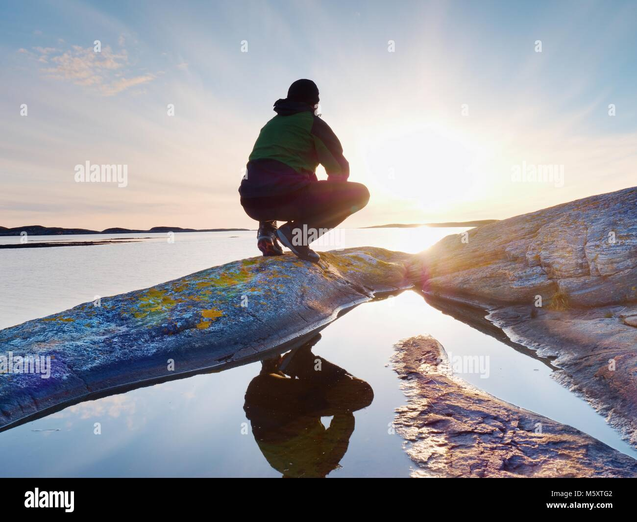 Alone tourist man sitting on a rocky lakeshore and thinking. Relaxing at  a beautiful multicolor sunset above free - Stock Image