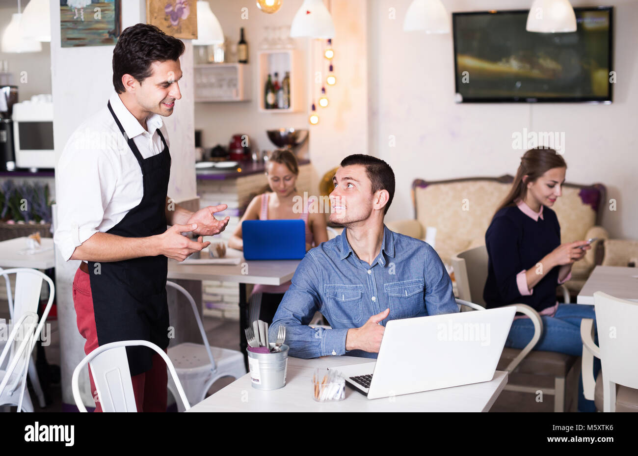Male guest of comfy confectionery giving order to welcoming waiter - Stock Image